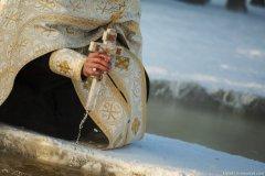 Батюшка окунает крест в воду, тем самым освячивая её